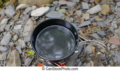Men's hands break the egg into a frying pan in a tourist camping