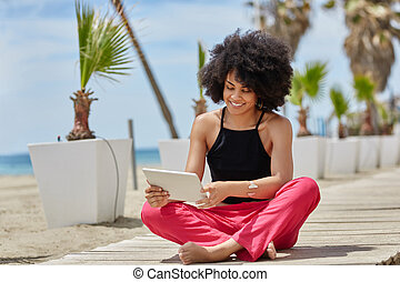 Happy afro american woman sitting crossed legs using tablet...