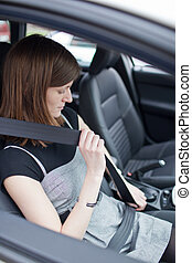 Road safety concept - Pretty young woman fastening her seat...