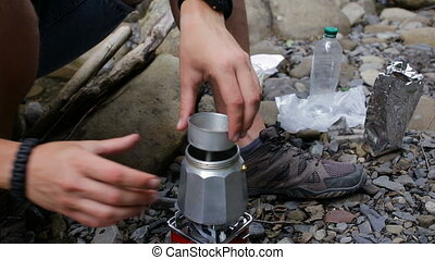 A tourist guy pours coffee into a coffee maker in a campsite...