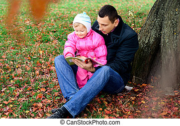 Father and daughter sitting under a tree Fall