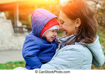 mother holding baby outdoors in autumn
