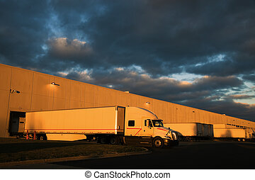 Dramatic sunset above distribution warehouse. Semi Truck...