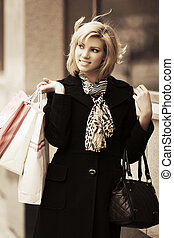 Happy young fashion woman with shopping bags at the mall...