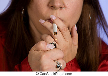 Woman lighting a cigarette - Close up of a woman lighting a...