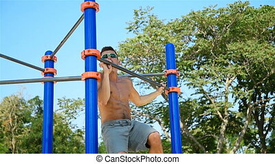 Man Pulls Himself Up On Horizontal Bar In Turn With His Left...