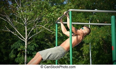 Muscular Man Does A Horizontal Pull On The Bar. Slow Motion...