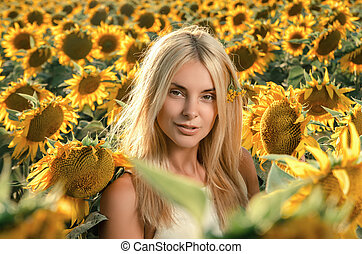 young beautiful woman on blooming sunflower field