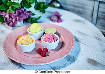 Selection of gourmet flavours of Italian ice cream in vibrant colors served in individual porcelain cups on an old rustic wooden table in an ice cream parlor, angle view jpg