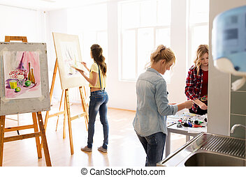 woman artists with colors painting at art school -...