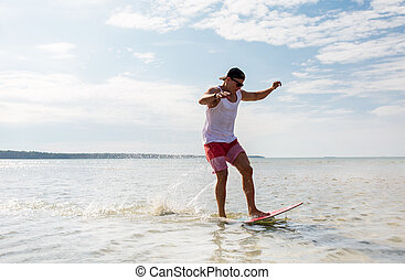 young man riding on skimboard on summer beach -...