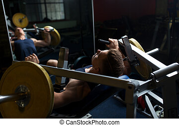 man doing chest press on exercise machine in gym - sport,...