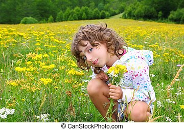 Girl picking flowers in yellow spring meadow beautiful...