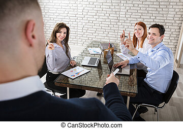 Businessman Asking Question In Meeting - Businessman Asking...