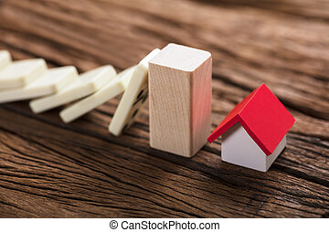 Block Stopping Domino Pieces Representing Home Insurance -...