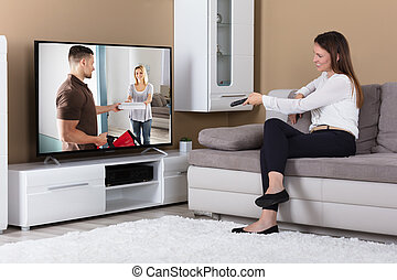 Smiling Woman Sitting On Sofa And Watching Television -...