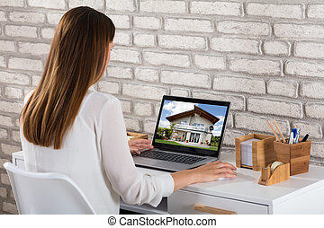 Businesswoman Looking At House On Laptop - Young...