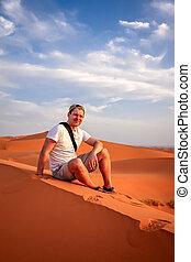 Tourist resting on the sand dunes of Merzouga - Tourist...