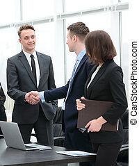 handshake business partners at a meeting in the office -...