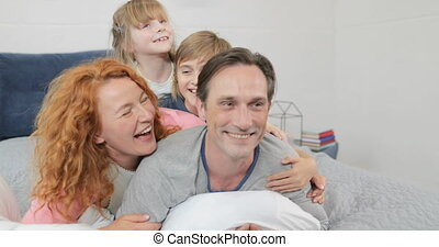 Family Happy Smiling Lying Together On Father In Bedroom, Cheerful Parents With Children In Morning