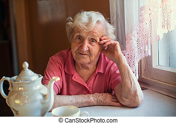 Portrait of an elderly woman in her home at kitchen.