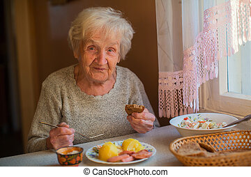 An elderly woman eats sitting at the table.
