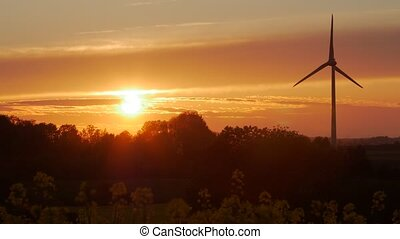 Wind turbines farms with rays of light at sunset