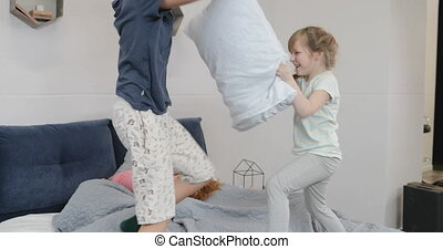 Happy Children Having Fun In Parents Bedroom Fighting Pillows In Morning While Mother And Father Lying Pn Bed Laughing