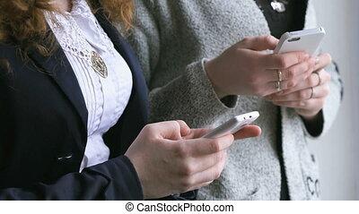 Schoolgirls hold smart phones in hands indoors