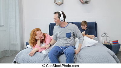 Happy Family Using New Headphones Listening To Music In...