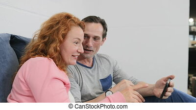 Adult Couple Using Cell Smart Phone Lying In Bed Over...