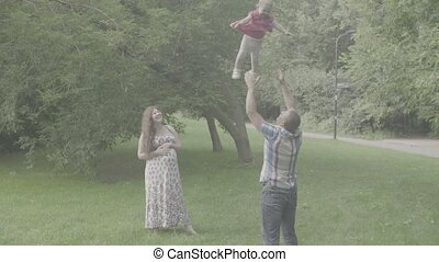 Mom and dad holding baby and swinging her - Mom and dad...