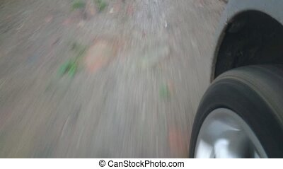 Driving shot with mounted camera. Point of view - driving during rainy weather. POV - driving on unpaved road, dirt road. Driving through puddles. Audio footage. Sound of engine