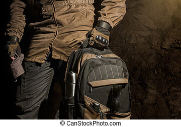 Backpack and gear composition. - Man in storm jacket and...