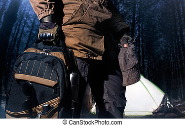Backpack and gear woods composition. - Man in storm jacket...