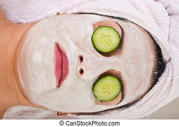 Detail of woman with facial mask and cucumber