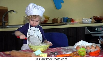 Beautiful child girl take of chef hat and play with flour....