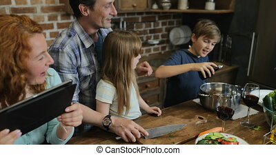 Family Cooking Together In Kitchen Using Recipe From Tablet...