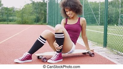Flirty woman on skateboard - Young ethnic girl in trendy...