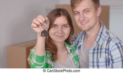 Young happy couple with boxes and holding flat keys - Young...