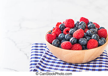 fresh blueberry and rasberry on wood bowl
