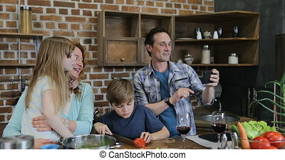 Father Taking Selfie Photo Of Happy Family Cooking In Kitchen Together Preparing Meal At Home