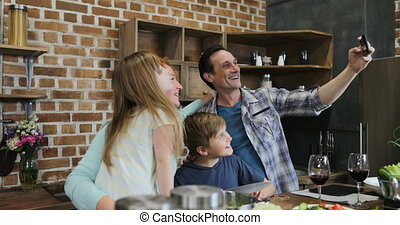 Father Use Cell Smart Phone Taking Selfie Portrait Of Happy Family Cooking In Kitchen Together At Home