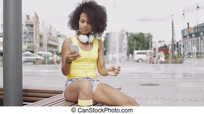 Sportive girl using smartphone on bench - Beautiful ethnic...