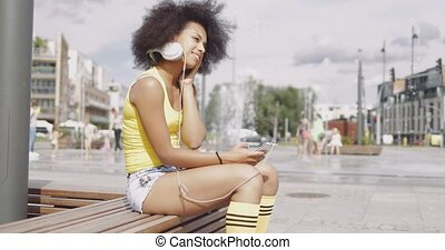 Model in headphones sitting on bench - Side view of...