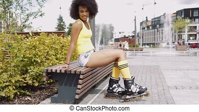 Stylish woman in rollers posing on bench - Young charming...