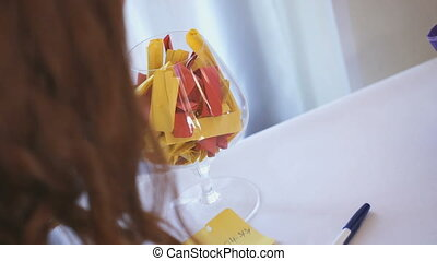Male hand putting a note in a large glass goblet - Wedding...
