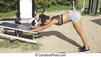 Girl stretching in park gym - Side view of young fit woman...