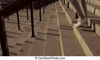Tracking shot of a sporty man walking down the staircases -...