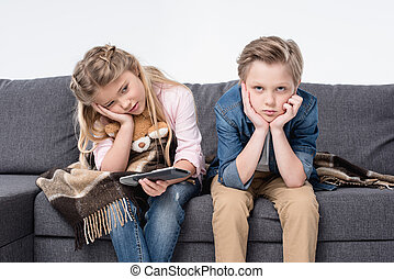 pre-adolescent bored brother and sister sitting on sofa and...